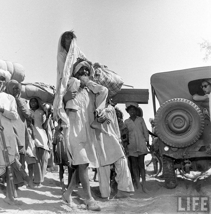 A Sikh carrying his wife on his shoulders