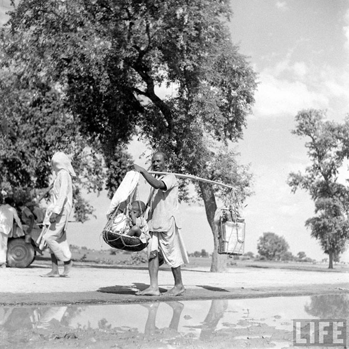 A Man carrying his 5-yr. old son and belongings with balancing pole to escape anti-moslem Sikhs